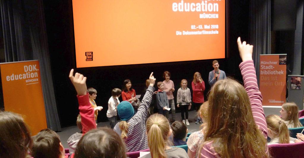 SchülerInnen melden sich in einem Kinosaal. Eine Gruppe mit Florian Geierstanger steht auf der Bühne vor der Leinwand mit orangem DOK.fest Logo.